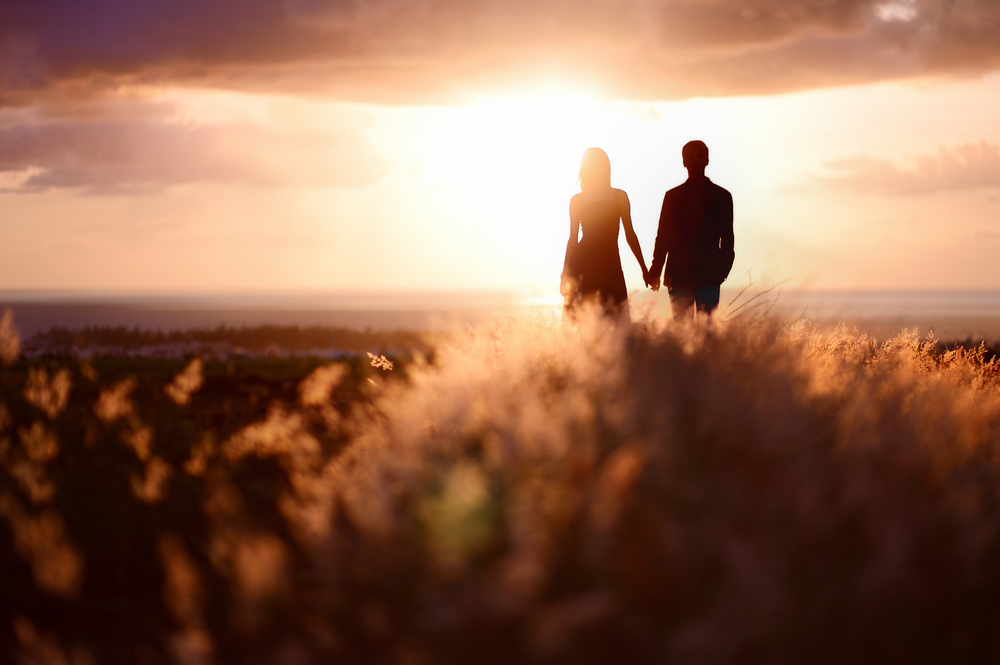 couple walking into sunset